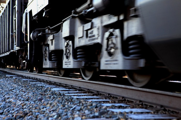 Close-up of a locomotive's wheels as it moves along a rail track.