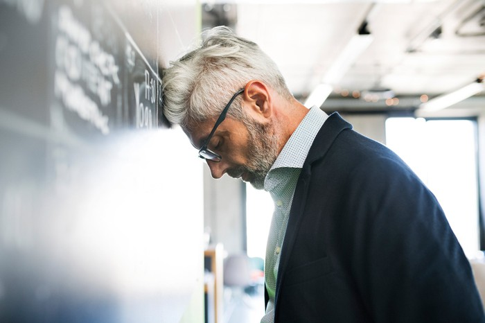 Gray-haired man in glasses, collared shirt, and suit jacket leaning head against wall