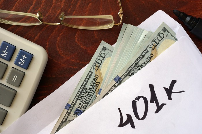 Envelope labeled 401k with hundred-dollar bills sticking out on wooden surface next to calculator and glasses