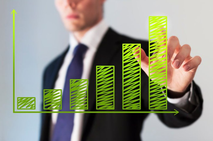 A businessman pointing to rising green columns on a chart.