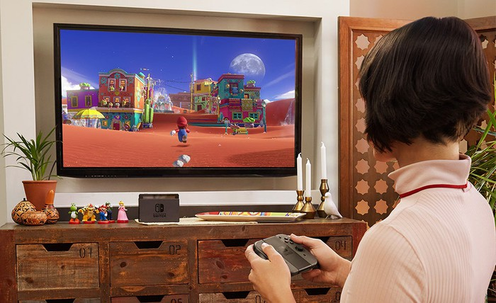 Woman playing a Mario game on a TV with the Nintendo Switch console