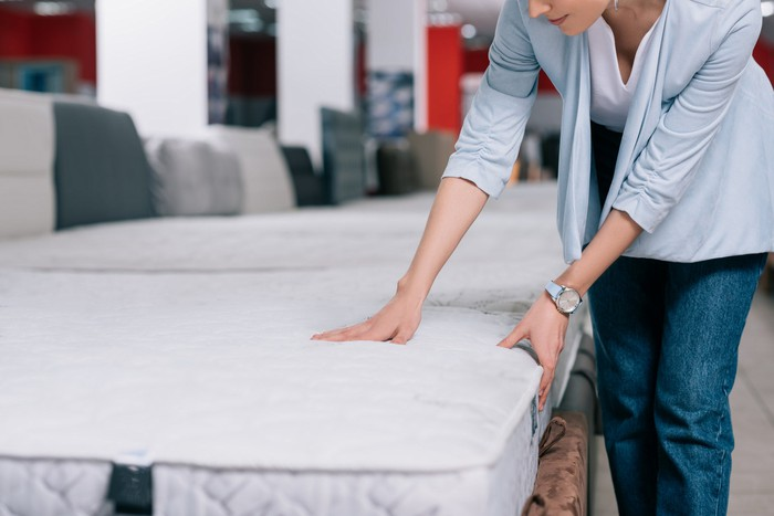 A woman tests a mattress in a store.