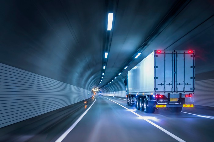 A commercial truck passes through an illuminated modern tunnel.