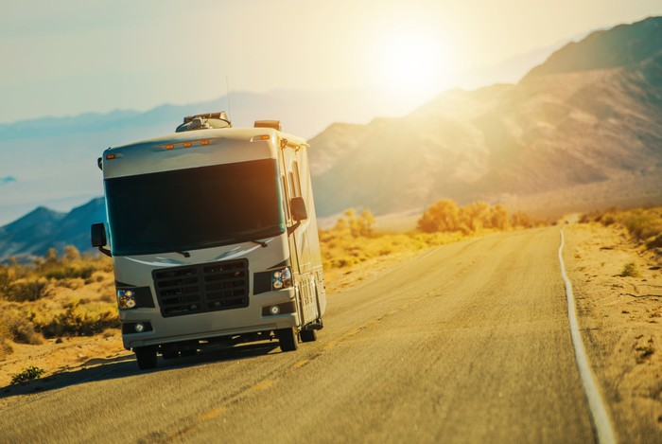 An RV drives along a rural road as the sun sets behind it.