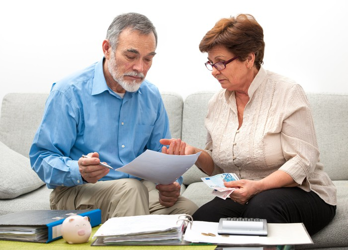 Older man and woman looking at documents; on a table in front of them are binders and a calculator