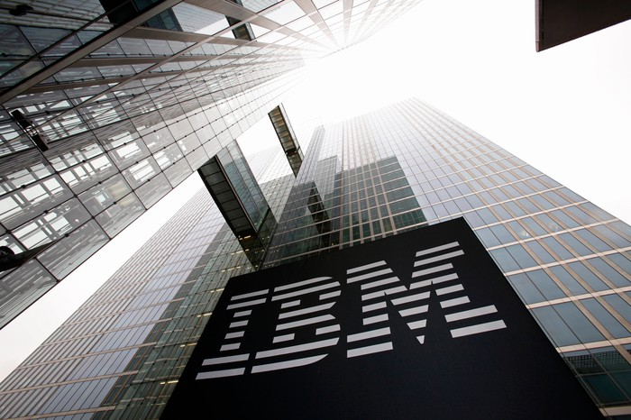 Photo taken upward from the foot of a tall, glass-clad office building, highlighting a large IBM logo.