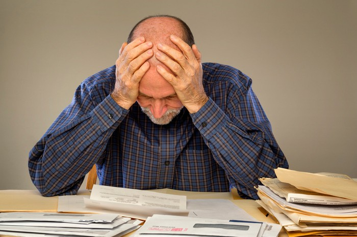 Older man sitting at a table and holding his head while looking at papers and folders spread out in front of him.