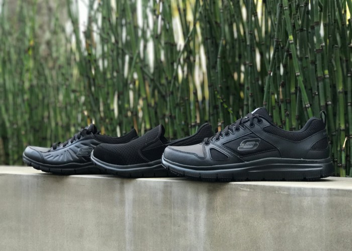 Black Skechers shoes lined up on top of a concrete wall with bamboo in the background.