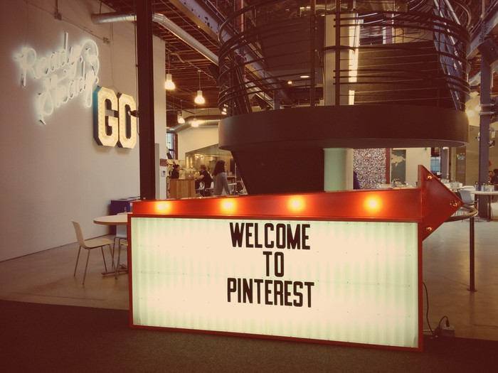Decor at Pinterest in France consisting of a board that says Welcome to Pinterest with a lit-up arrow on top.