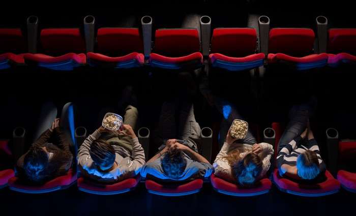 Overhead view of people eating popcorn in movie-theater seats