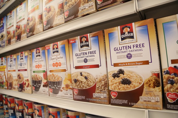 A row of Quaker cereal boxes on a shelf in a store.