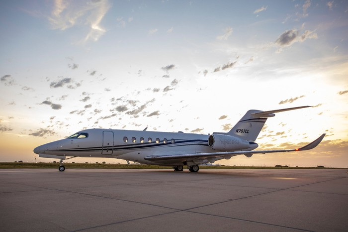 A Citation Longitude business jet in front of a sunset.