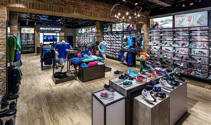 The interior of a Skechers retail store. Shoes and other sports apparel is displayed on shelves and on boxes in the middle of the floor.