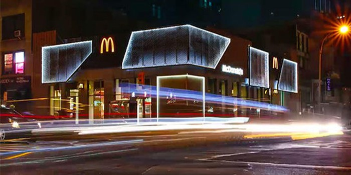A neon lit McDonald's on the corner of an intersection