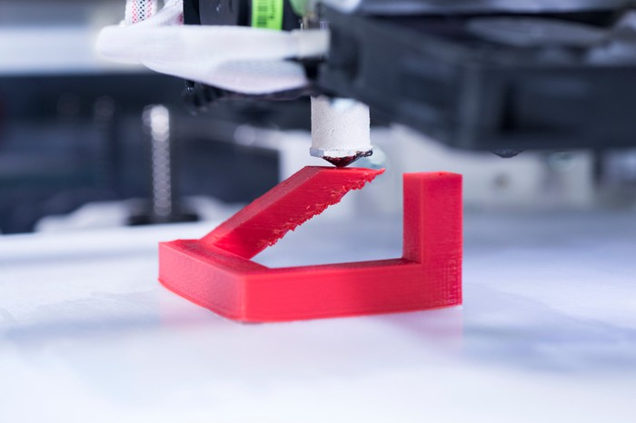 Close-up of a 3D printer printing an unidentifiable red plastic object.