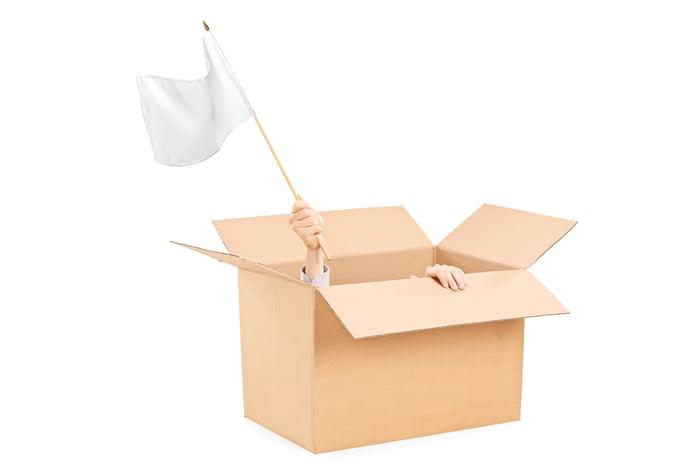 Un homme se cachant dans une boîte en carton brandit un drapeau blanc.