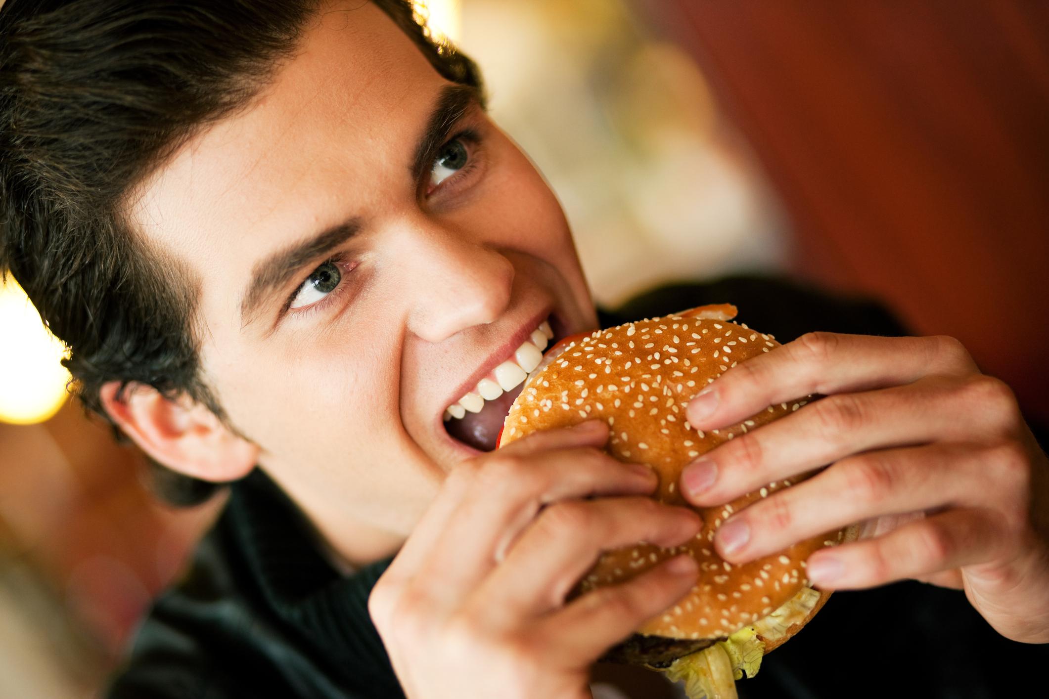 A man takes a bite out of a burger.