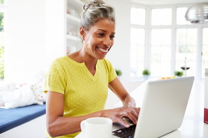 Smiling older woman using laptop.