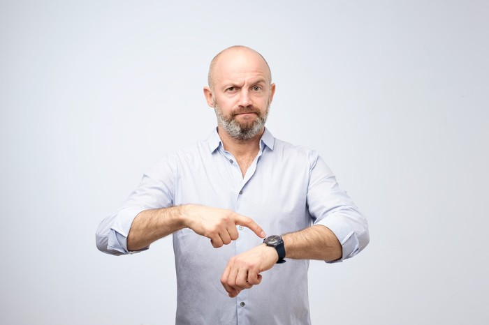 Man pointing at watch with annoyed expression
