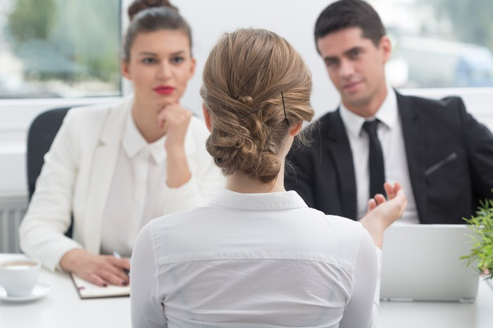Woman talking to two professionals across a table in a business setting.