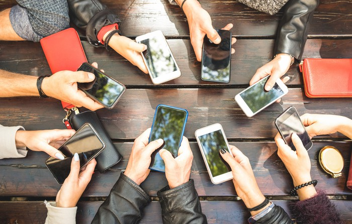 A group of hands holding mobile phones in a circle around a table.