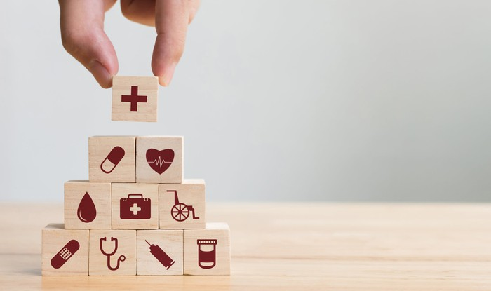 Hand placing a wood block on top of a pyramid of wood blocks, all of which have healthcare-related images printed on them