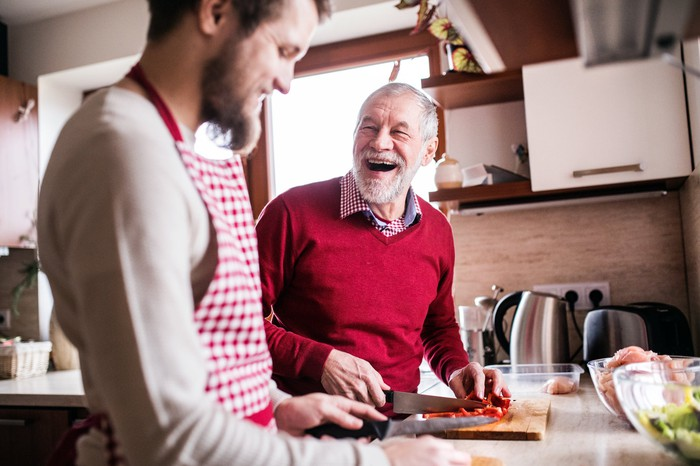 Younger male adult and older male adult prepping food in kitchen