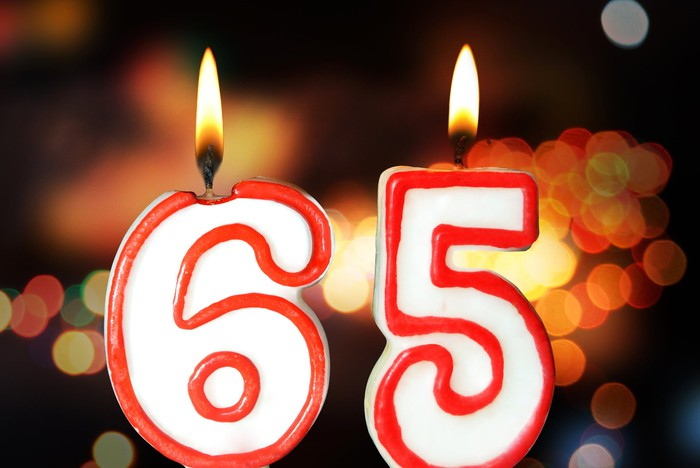 Candles in the shape of the number 65 lit in front of a black background with orange dots