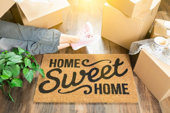 Woman sitting on floor next to plants, moving boxes, and mat that says home sweet home