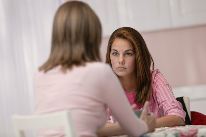 Teenage girl with serious expression sitting across the table from an older woman