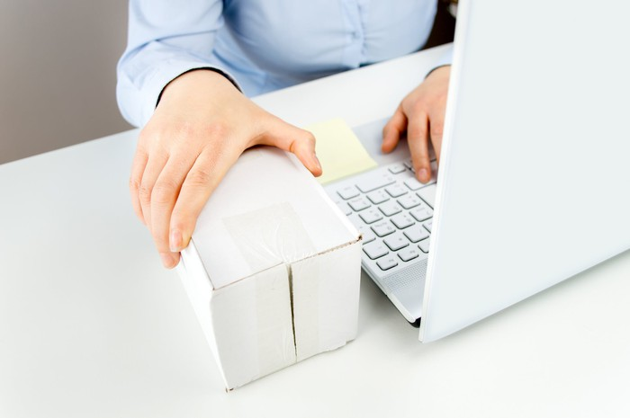 Person holding a small shipping box next to a laptop computer