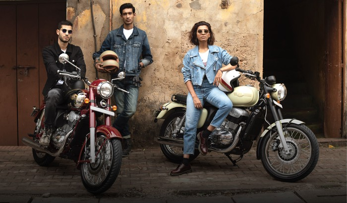 Two men and a woman with Jawa motorcycles.