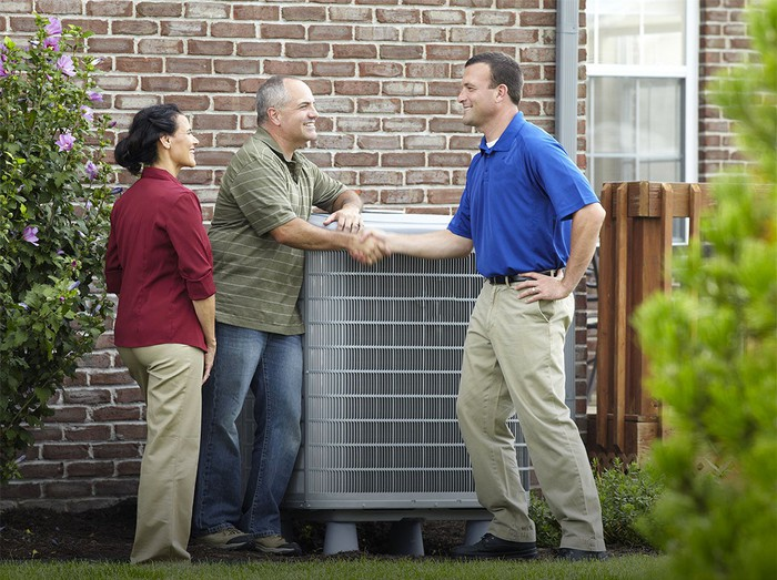Two people shaking hands next to an air conditioning unit with a third person watching, next to a brick house with nearby shrubs.