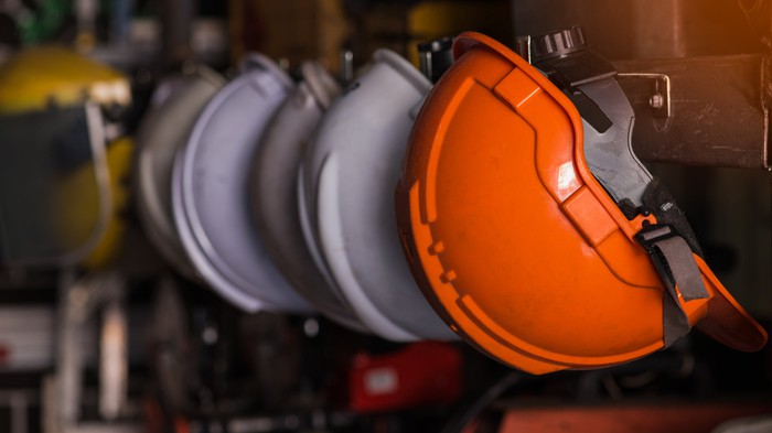 A colorful row of hard hats hanging on hooks.