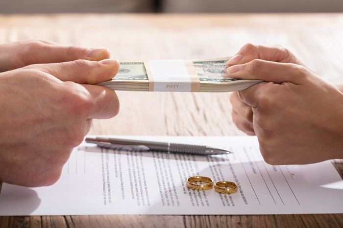 Couple fighting over money over divorce papers