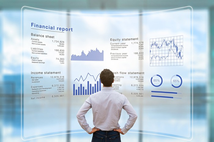 A businessman looks at financial charts projected on a digital screen.