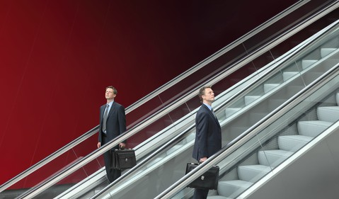 Businessman going up and down two escalators