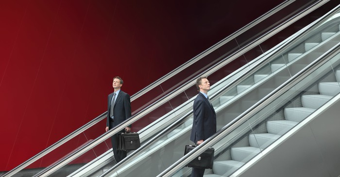 Businessmen going up and down two escalators