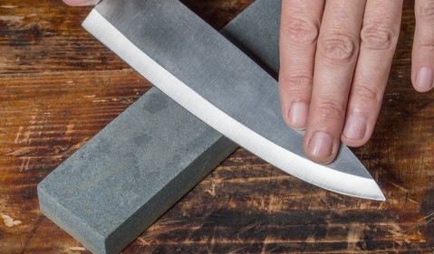 Knife being sharpened on a whetstone