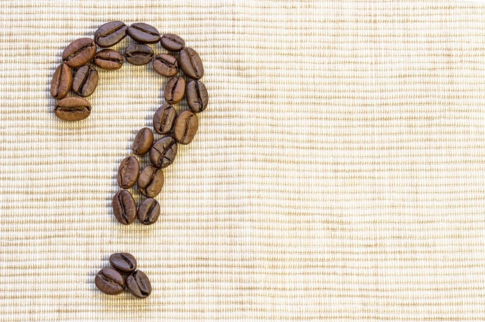 Coffee beans arranged in the shape of a question mark.