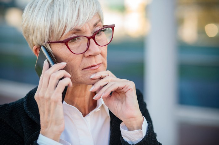 Older, short-haired woman on cell phone with serious expression