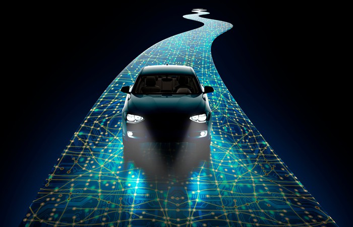 A self driving car seen from the  front drives through the dark on a sensored road with headlights on.