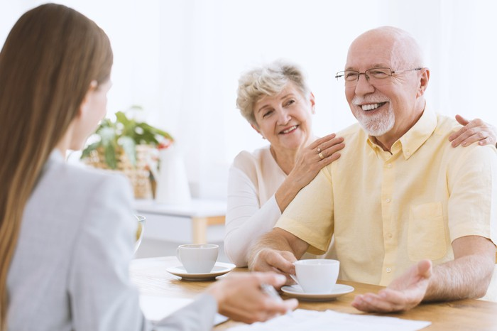 Young woman sitting across from smiling older couple with mugs in front of them