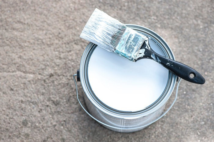 A can of white paint with a paintbrush on top of it.