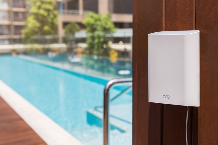 Outdoor Netgear Orbi router mounted on wood wall by pool.