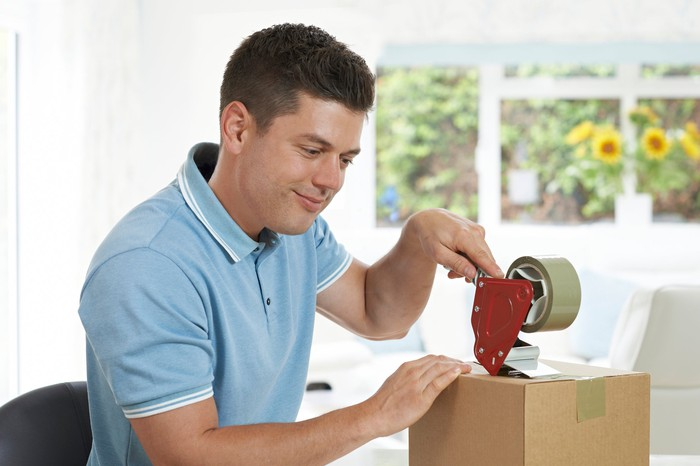A man taping a package shut.