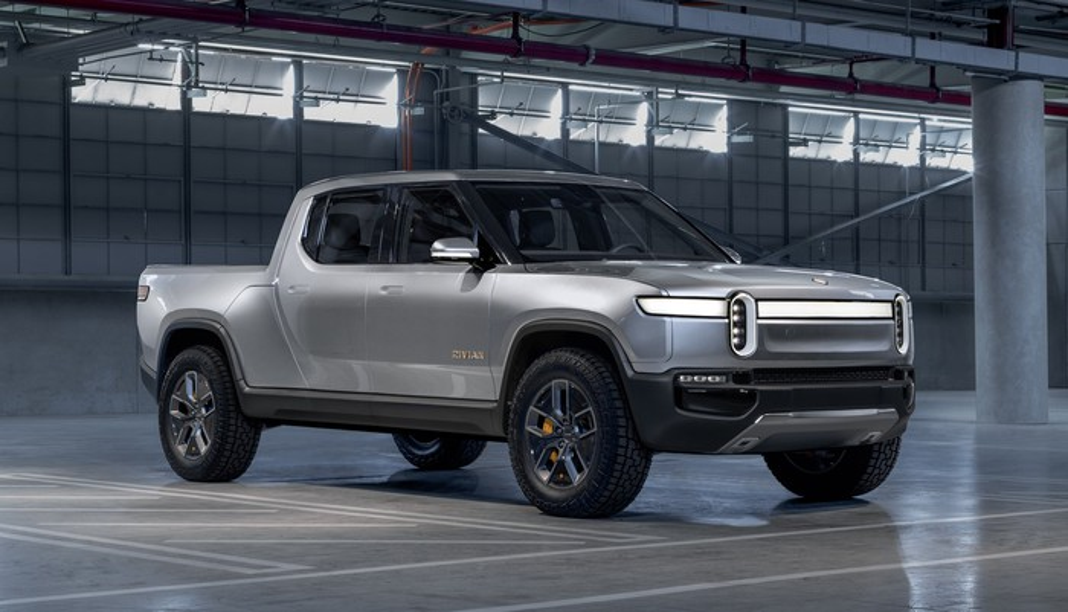 A Rivian R1T, a sleek, futuristic-looking full-size electric pickup truck