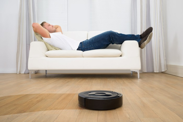 A man reclines on a white couch as a robotic vacuum cleans a dirty wood floor.