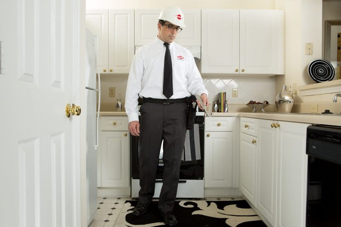 Orkin Man holding a flashlight and examining a kitchen.