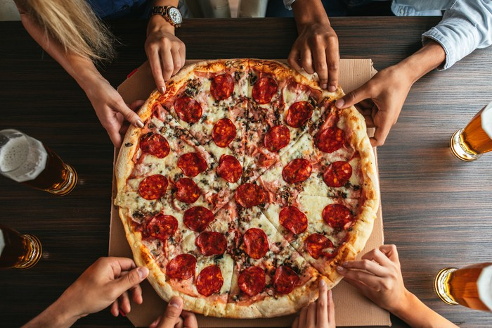 Hands grabbing for a large pizza pie.